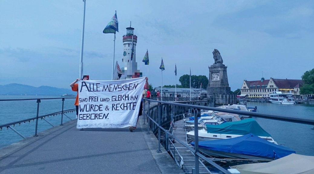 Etwa 50 Personen demonstrieren am Lindauer Hafen im Rahmen des Seebrücke-Aktionstages für sichere Häfen.