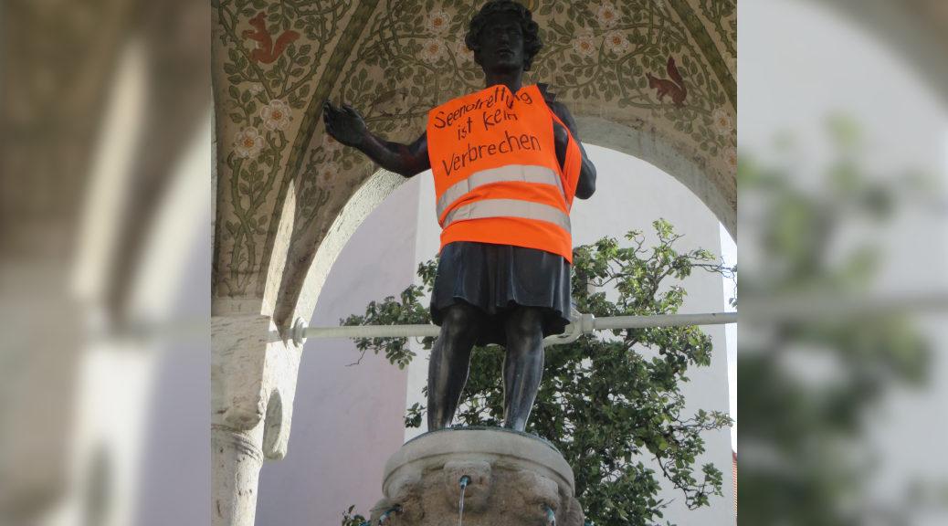 Aktivisten der Seebrücke brachten unter anderem an der Heiligenstatue auf dem Kirchplatz in Kempten eine Rettungsweste mit der Aufschrift »Seenotrettung ist kein Verbrechen« an.