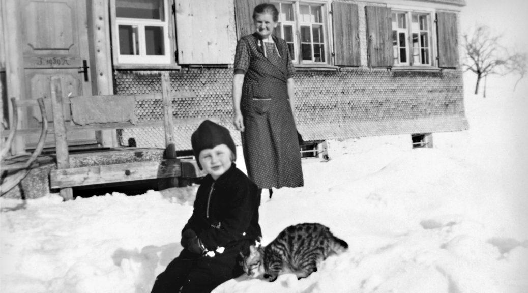 Gabi mit roter Mütze und Katze im Schnee.