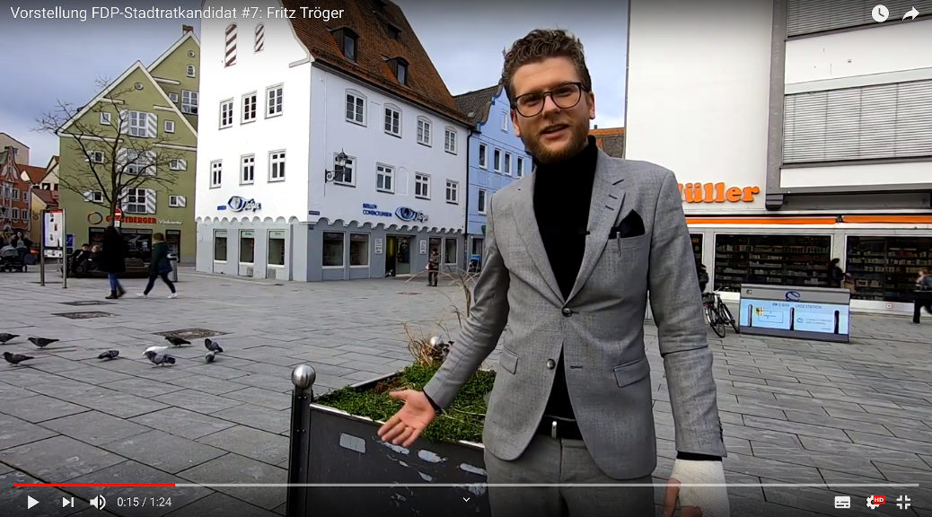 Vor seinem Optikergeschäft in der Memminger Innenstadt stellt sich der Jungunternehmer Fritz Tröger als Stadtratskandidat der FDP vor. (Screenshot Youtube)
