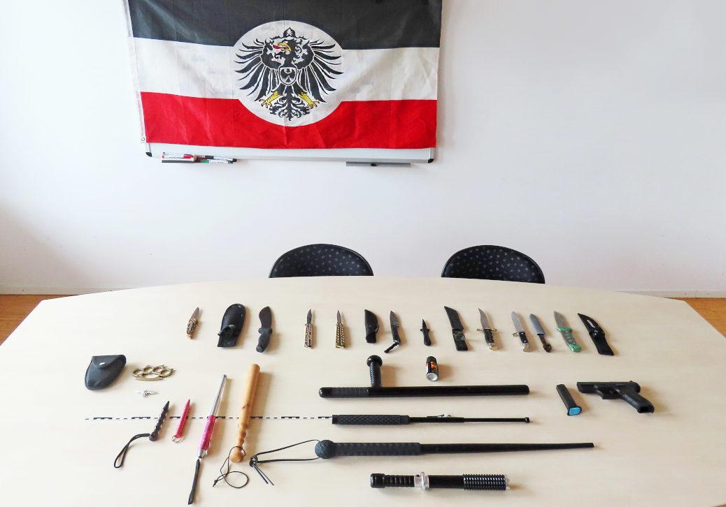 In einer Wohnung im Unterallgäu findet die Polizei bei einer Durchsuchung neben Reichsflagge und Hakenkreuz eine Schusswaffe, Schlagringe, Schlagstöcke und Butterflymesser. (Bild: Polizei)